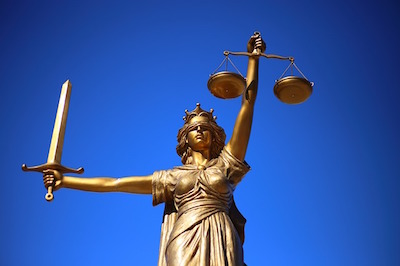 Photo of Lady Justice Holding a Sword and the Scales of Justice